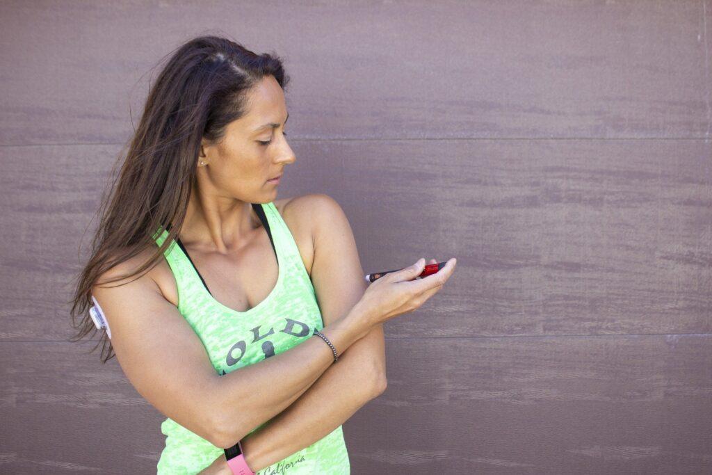 Mulher utilizando caneta de insulina durante atividade física por conta do diabetes